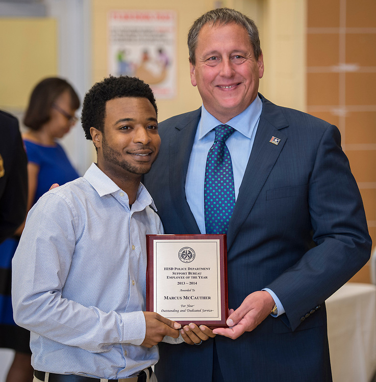 Marcus McCauther receives the Support Bureau Employee of the Year award from Chief Robert Mock, right, during the Houston ISD Police awards banquet at Thompson Elementary School, August 15, 2014.