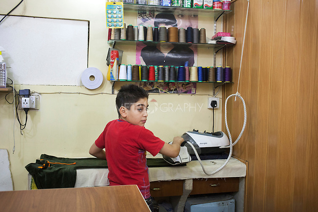 21/10/14. Erbil, Iraq. Wassam irons a pair of trousers at his uncle Amir's tailoring shop in Ainkawa. Wassam wants to visit the shop as his uncle works alone, and because he would like to learn about tailoring.