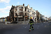A firefighter attends the scene near a burnt out building in the London borough of Croydon. London saw the beginnings of riots on Saturday evening, after a peaceful protest in response to the shooting by police of Mark Duggan during an attempted arrest, escalated into violence. By the third night of violence, rioting and looting had spread to many areas of the capital and to other cities around the country.