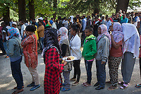 Italy. Lombardy Region. Como. Homeless african migrants living in the park below the San Giovanni railway station. Women and men stand in live in order to receive food provided by the swiss NGO Firdaus. A non-governmental organization (NGO) is a not-for-profit organization that is independent from states and international governmental organisation. A hijab is a veil that covers the head and chest, which is particularly worn by some Muslim women in the presence of adult males outside of their immediate family. 12.08.2016 © 2016 Didier Ruef