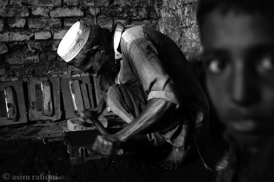 a man prepares moulds from which the principal portions of the guns are prepared.  the moulds are filled with metal dust and then heated and melted to created the main firing mechanisms of pump action shot guns.  darra adam khel, tribal areas, pakistan.  september 2003.&amp;#xA;&amp;#xA;copyright asim rafiqui 2003<br />