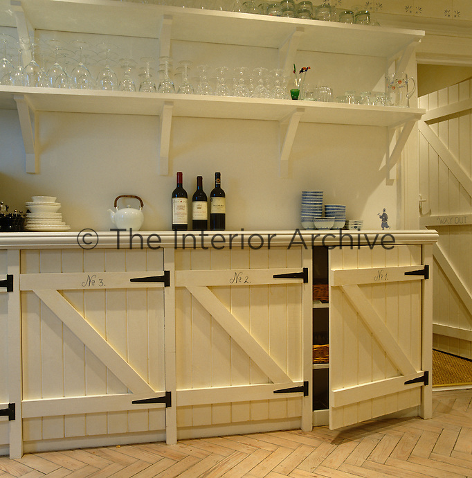 Shelves used to store wineglasses are mounted above a row of kitchen cupboards designed to resemble stable doors
