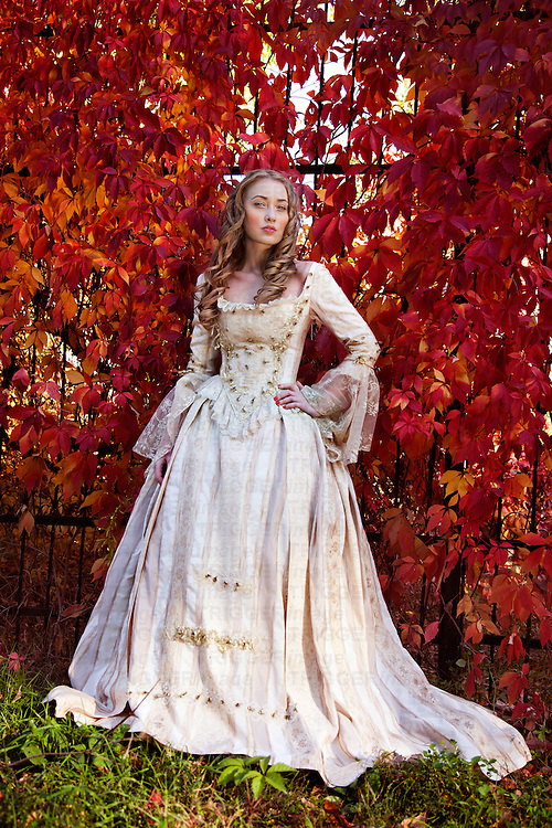 A young woman wearing a period regency costume standing alone outdoors