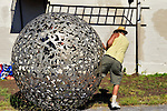 "Huntington, New York, U.S. 24th August 2013. STEVEN ZALUSKI, performance artist, is in stepping into his rolling metal sculpture ""Sphere of Hope"" at the art event ""Off the Walls"" Block Party, by SPARKBOOM, a Huntington Arts Council project created to help emerging artists, showcase talents, and help its artistic family network. The sculpture of human shapes welded together has a round opening big enough for a person to enter, Zaluski's studio is in Ronkonkoma."