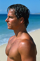 Profile of a wet shirtless young man at the beach