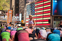 "Yoga instructor Bethany Lyons in Times Square in New York during a Power Yoga class on the first day of summer, Saturday, June 21, 2014. The 12th annual Solstice in Times Square, ""Mind Over Madness"",  stretches the yogis' ability to block out the noise and the visual clutter that surround them in the Crossroads of the World. (© Richard B. Levine)"