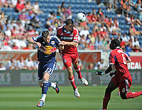 Chicago defender Austin Berry (22) heads the ball over New York forward Kenny Cooper (33).  The Chicago Fire defeated the New York Red Bulls 3-1 at Toyota Park in Bridgeview, IL on June 17, 2012.