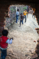 Children of commercial sex workers play in the compound of the new Non-Formal Education (NFE) center that is being constructed in the Mau Red Light area in Mau, Uttar Pradesh, India on 16 November 2013. The children proudly take ownership of the Guria NFE center and often spend their time near the nearly complete building in anticipation of the school's reopening.