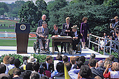 United States President George H. W. Bush signs the Americans with Disabilities Act of 1990 into law during a ceremony on the South Lawn of the White House in Washington, D.C. on July 26, 1990. Pictured (left to right): Evan J. Kemp, Jr., Chairman, U.S. Equal Employment Opportunity Commission; Reverend Harold Wilke; President Bush; Sandra Parrino; Justin Dart; and unidentified interpreter.  The act prohibited employer discrimination on the basis of disability. <br /> Credit: Ron Sachs / CNP
