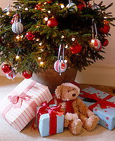 Presents are arranged at the base of a Christmas tree where a teddy bear sits expectantly