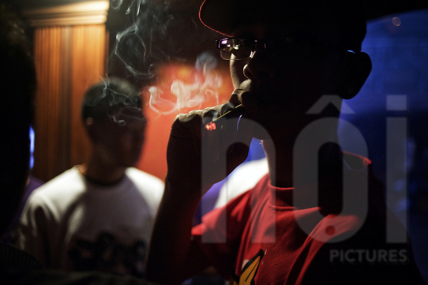 Anonymous hip-hop fan smoking marijuana during a rap concert in Yangon.