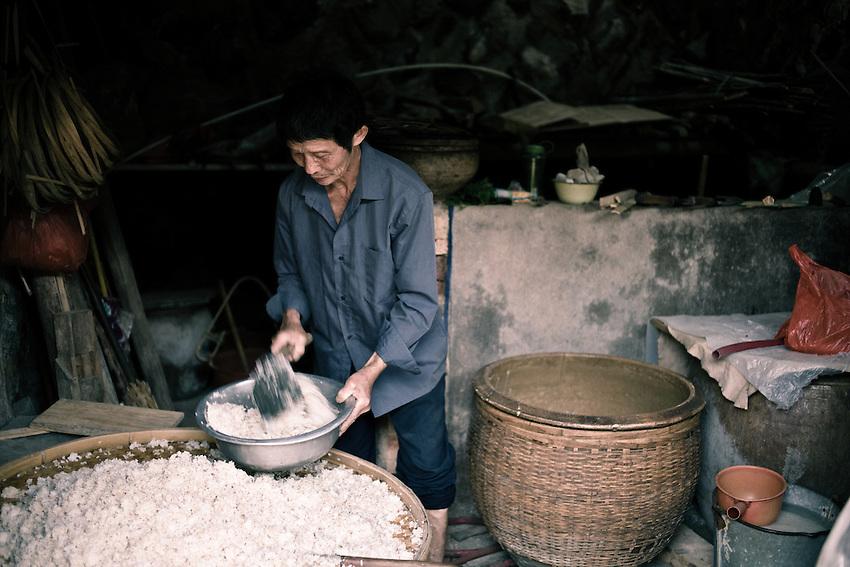 """Dans une vallée à l'écart, plusieurs villages perdurent dans l'autosuffisance du travail rural. Ici un homme prépare avec son épouse le Choujiu, un alcool de riz très fort, titrant près de 50° . 6 kuais (70cts d'euros ) la bouteille d'un litre...""""garanti sans méthanol"""" selon les vendeurs."""
