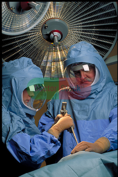 orthopedic surgeon and nurse wearing clean suits with self-contained air units perform joint replacement surgery on a hip