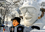 A young boy mimics the signature pose of a popular comedian during the Sapporo Snow and Ice Festival in Sapporo City, northern Japan. Around 2 million people visit the city to see the hundreds of hand-crafted snow and ice sculptures that have graced the Sapporo Snow and Ice Festival since its inception in 1950.