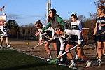 23 February 2017: Notre Dame assistant coach Katie Powell (in green) throws a ball out for Molly Cobb (22) and Katherine Eilers (right). The Elon University Phoenix hosted the University of Notre Dame Fighting Irish at Rudd Field in Elon, North Carolina in a 2017 Division I College Women's Lacrosse match. Notre Dame won the game 16-7.