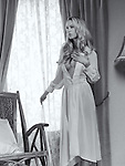 Beautiful young woman with long blond hair wearing a white night gown standing by the window. Black and white.