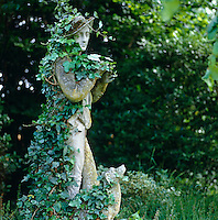 An ivy-clad stone statue of a shepherd and his dog stands in a corner of the garden