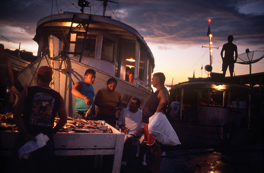 Amazon river fishermen sell their waress at the Panair docks in Manaus, Brazil, Monday, January 9, 2006. Fishmongers from the city's public markets arrive in the wee hours of the morning to buy their stocks for the day directly from the boats. The Amazon river system boasts more different species of fish than the Atlantic Ocean, but as population increases, so does the pressure on fish stocks in the vast river. (Kevin Moloney for the New York Times)