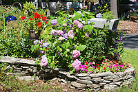 Planting flowers around a mailbox with stone wall raied bed, gazing ball, driveway,hammock, hydrangea, impatins, hanging container pot of red geraniums, antique car convertible. Curb Appeal landscaping