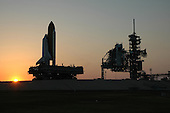 Kennedy Space Center, FL - May 19, 2006 -- The sun is setting as Space Shuttle Discovery nears its place on Launch Pad 39B at NASA's Kennedy Space Center. At right are the fixed and rotating service structures. First motion was at 12:45 p.m. EDT. The shuttle rests on a mobile launcher platform and made the 4.2-mile journey from the Vehicle Assembly Building via the crawler-transporter beneath the platform. The rollout is an important step before launch of Discovery on mission STS-121 to the International Space Station. Discovery's launch is targeted for July 1 in a launch window that extends to July 19. During the 12-day mission, Discovery's crew will test new hardware and techniques to improve shuttle safety, as well as deliver supplies and make repairs to the station. .Credit: Dimitri Gerondidakis - NASA via CNP