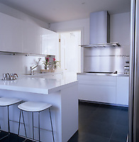 The white contemporary kitchen has a slate tiled floor, white lacquer cabinets by Boffi and bar stools by Jasper Morrison
