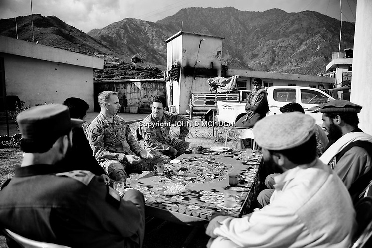 US Army Lieutenant Colonel Dan Wilson (3L), Battalion Commander of 2/27 Infantry, 25th Infantry Division, and  Mohammed Ishmael (left with back to camera), Police Chief of Ghaziabad District, eat and chat in Nichigam District Centre in northern Kunar, 20 November 2011. Four days later, on 09 Dec, Ishmael was killed with 5 others when a 12 year old suicide bomber blew himself up in the village. (John D McHugh)