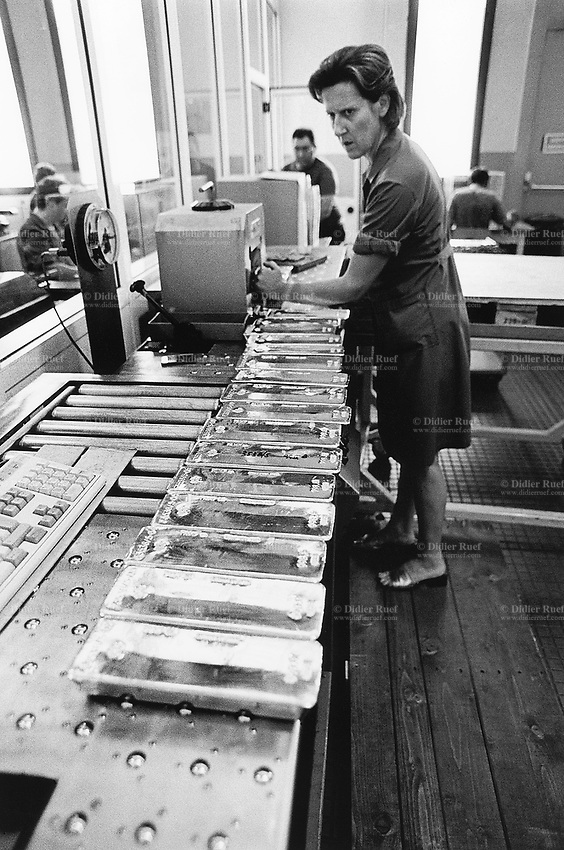 Switzerland. Castel San Pietro. 10 km from Chiasso. Firm PAMP SA. Gold refinery. The high technology provides an integrated service in precious metals, from pick-up of doré at the mine trough assaying, refining, hedging and delivery of bars troughout the world. A woman worker weighs with precision gold bars. © 1998 Didier Ruef