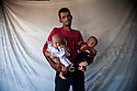 A father proudly takes a portrait with his twins. Severely wounded while working (illegally, the only option available to him) on an Israeli construction project, he spends his day in pain and is unable to find work to provide for this family.