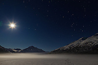 A full moon illuminates Bold Peak and ground fog on frozen Eklutna Lake in Chugach State Park in Southcentral Alaska. Winter. Evening.