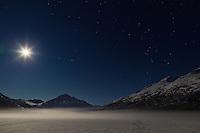 A full moon illuminates Bold Peak and ground fog on frozen Eklutna Lake in Chugach State Park in Southcentral Alaska. Winter. Evening.