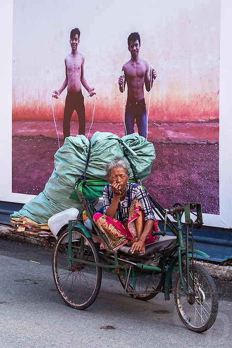 A women and her belongings in a cart in the street of Phnom Penh, behind her a Photo Mural,Cambodia