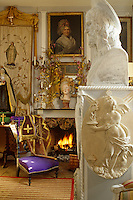A purple 'priere dieu' stands next to the fire in a room that is filled with religious objects