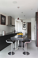 A granite-topped breakfast bar extends from the central kitchen island, which gives the narrow kitchen an illusion of extra space