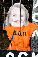"Next to a sign for Spencer White Building and Remodeling Contractor and a Trump campaign sign, an effigy of Democratic presidential nominee Hillary Clinton appears to be in jail and surround by the words ""Lock her up!!,"" ""Corrupt / CNN, ABC, CBS, NBC,"" and ""Handcuffed Together!! Stronger Together!!!"" in Troy, New Hampshire, on Fri., Nov. 4, 2016."