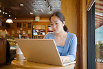 Korean female student of 27 years sits at table with laptop computer in cafe