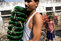 A man is transporting unfinished glass bracelets from a house to another one on the road connecting two sections of the slum surrounding Firozabad, renowned as the 'glass city', in Uttar Pradesh, northern India. Due to extreme poverty, over 20.000 young children are employed to complete the bracelets produced in the industrial units. This area is considered to be one of the highest concentrations of child labour on the planet. Forced to work to support their disadvantaged families, children as young as five are paid between 30-40 Indian Rupees (approx. 0.50 EUR) for eight or more hours of work daily. Most of these children are not able to receive an education and are easily prey of the labour-poverty cycle which has already enslaved their families to a life of exploitation. Children have to sit in crouched positions, use solvents, glues, kerosene and various other dangerous materials while breathing toxic fumes and spending most time of the day in dark, harmful environments. As for India's Child Labour Act of 1986, children under 14 are banned from working in industries deemed 'hazardous' but the rules are widely flouted, and prosecutions, when they happen at all, get bogged down in courts for lengthy periods. A ban on child labour without creating alternative opportunities for the local population is the central problem to the Indian Government's approach to the social issue affecting over 50 million children nationwide.