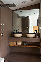 In the bathroom a pair of matching travertine basins is situated on a stone washstand in front of a large mirror with an adjacent shower mounted on the grey stone wall