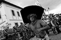 An Indian, wearing a large cardboard hat, dances in front of the police block during the Inti Raymi (San Juan) festivities in Cotacachi, Ecuador, 29 June 2010. 'La toma de la Plaza' (Taking of the square) is an ancient ritual kept by Andean indigenous communities. From the early morning of the feast day, various groups of San Juan dancers from remote mountain villages dance in a slow trot towards the main square of Cotacachi. Reaching the plaza, Indians start to dance around. They pound in synchronized dance rhythm, shout loudly, whistle and wave whips, showing the strength and aggression. Dancers from either the upper communities (El Topo) or the lower communities (La Calera), joined in respective coalitions, seek to conquer and dominate the square and do not let their rivals enter. If not moderated by the police in time, the high tension between groups always ends up in violent clashes.