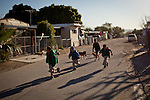 Schoolchildren run to the school bus at the Rancho Garcia trailer park in Thermal, Calif., March 9, 2012.