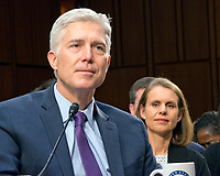 Judge Neil Gorsuch testifies before the United States Senate Judiciary Committee on his nomination as Associate Justice of the US Supreme Court to replace the late Justice Antonin Scalia on Capitol Hill in Washington, DC on Tuesday, March 21, 2017.  His wife, Marie Louise Grouch, watches over his shoulder at right.<br /> Credit: Ron Sachs / CNP /MediaPunch
