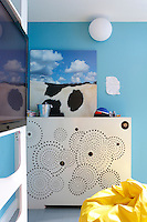 A panel perforated with a series of circles, disguises the radiator in this child's room