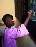 In Kaolak, Senegal, a young boy works at a chalkboard.