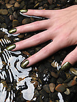 Closeup of woman hand with green fancy nail polish in water