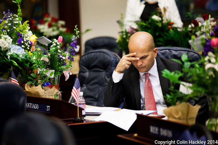 TALLAHASSEE, FLA. 3/4/14-Surrounded by flowers given to him and other House members to commemorate the opening day of the 2014 Legislative session, Rep. David Santiago, R-Deltona, studies a bill prior to the start of the House, March 4, 2014 at the Capitol in Tallahassee.<br /> <br /> COLIN HACKLEY PHOTO