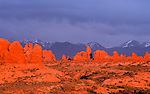 Fiery sunset casts a warm glow on The Windows, while clouds cloak the La Sal mountains in blue shadows, Arches  National Park, near Moab, Utah