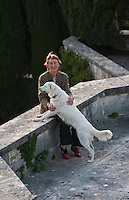 Benedetta Origo, Iris' daughter, sits on a stone wall with her dog