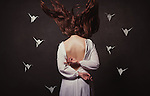 Conceptual image of female with long flying hair and paper cranes around her