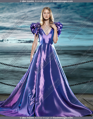 Young blond woman wearing a beautiful long blue dress, evening gown, at waterfront, artistic fashion portrait