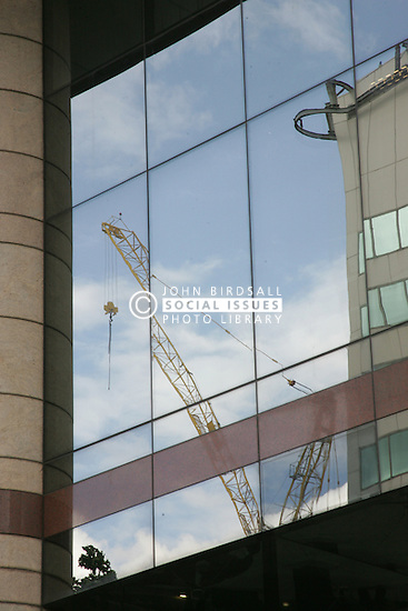 Construction crane reflected in office block window UK
