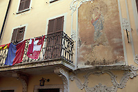 Switzerland. Canton Ticino. Astano. Facade of the Post hotel (Albergo della Posta). Religious painting on the wall. Swiss and tessin flags on a balcony. Closed shutters and windows. Astano is located in the Malcantone area. 16.03.2010 © 2010 Didier Ruef